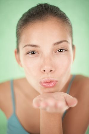 Attractive asian young woman blowing a kiss, closeup of the face. Shallow depth of field on green background. photo