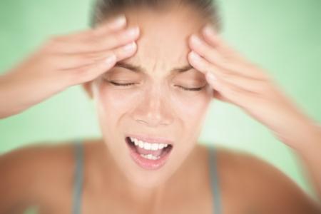 dolor de cabeza: La mujer teniendo una migra�a y dolor de cabeza, sosteniendo su cabeza en el dolor. Poco profunda de la profundidad de campo sobre fondo verde.