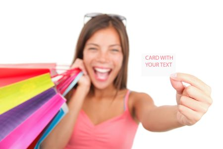 Shopping woman showing sign  business card. Very excited asian-caucasian model over seamless white. Shallow depth of field with focus on the blank sign  card.