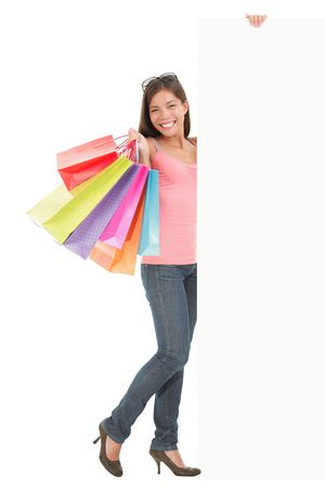 signboard: Shopping woman showing commercial sign. Full length picture of a beautiful young mixed race woman holding a blank billboard sign while standing with many shopping bags. Isolated on white background.