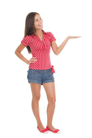 Showing product in full length.Young beautiful casual college  university student in summer clothes holding her arm out while presenting your product with an empty open hand. Gorgeous mixed race chinese  caucasian model isolated on white background.