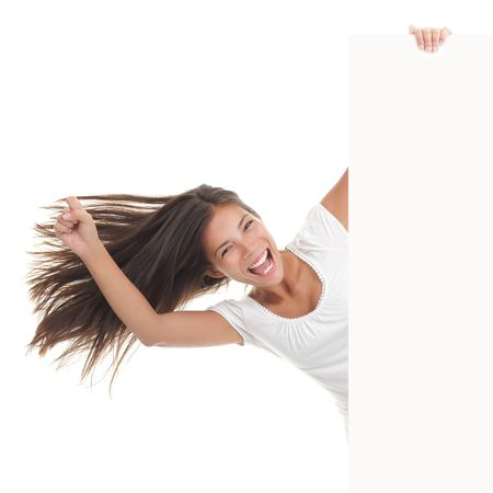 peeking: Billboard woman excited. Woman holding blank white placard  paper sign and being very happy and cheerful. Gorgeous mixed race chinese  caucasian model. Isolated on white background.