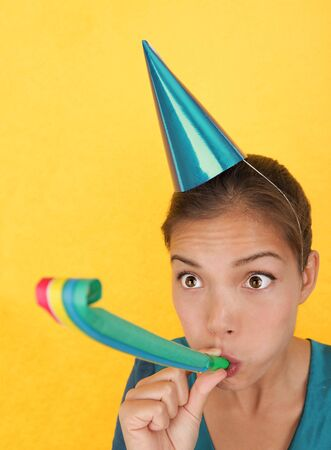 Funny party woman surprised on yellow background. Beautiful mixed race / asian caucasian model with party hat blowing a party blower at the camera.