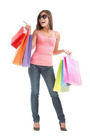 compras chica: Feliz de mujer ensaya un juego brillantes demostrando copia el espacio en el lado de compras. Longitud completa aislado sobre fondo blanco.
