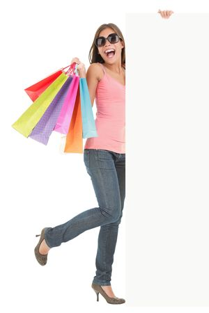 Shopping woman showing commercial sign. Full length picture of a beautiful young mixed race woman holding a blank billboard sign while standing with many shopping bags. Isolated on white background.