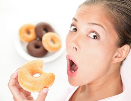 Unhealthy diet. Surprised woman caught eating donuts fast food.