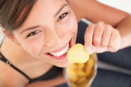merienda: Comer patatas chips  crisps.  Mujer bonita tener a una comida basura refrigerio mientras mirando la c�mara. Modelo de raza mixta adorable chino  cauc�sicos. Foto de archivo