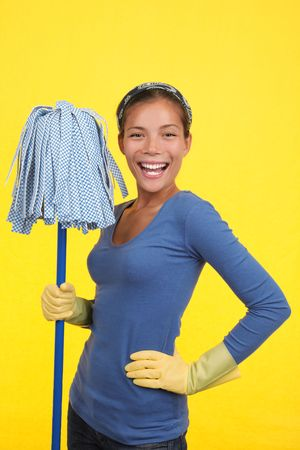 Cleaning woman happy and satisfied standing with a mop and wearing rubber washing up gloves on a yellow background.  Stock Photo
