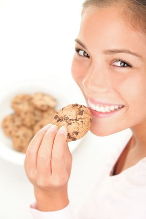 Chocolate chip cookies eating. Cute mixed race chinese / caucasian model on white background. Standard-Bild