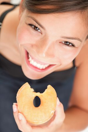 Donuts. Woman eating donut. Cute mixed race chinese  caucasian model. Stock Photo