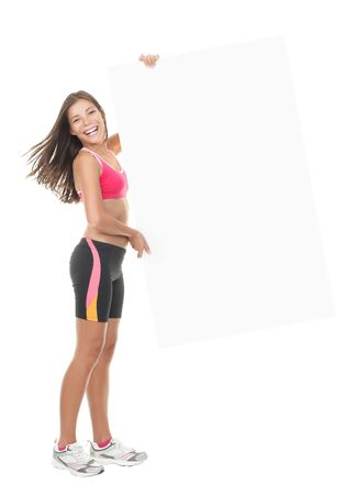 Beautiful fitness woman holding white blank sign / banner. Gorgeous smiling and energetic mixed race chinese / caucasian model isolated on white background.