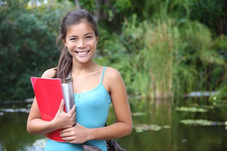 Student. Asian university student holding her books outdoors in the campus park. Cute young mixed race chinese / caucasian woman. Stock Photo - 6305257