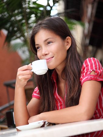 footpath: Cafe. Woman drinking coffee at a sidewalk cafe outdoors. Attractive mixed race chinese  caucasian model.