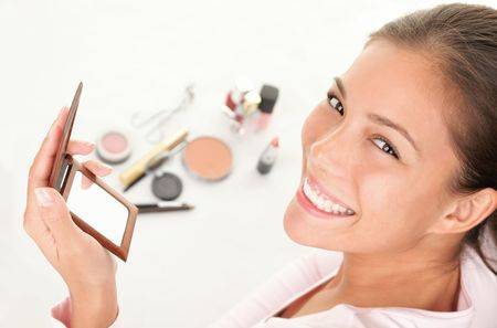 メイクアップ女性。かわいい化粧品女性化粧品を楽しんでします。