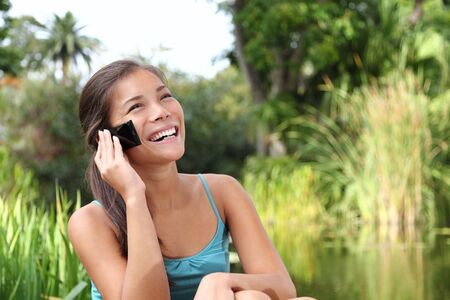 Student talking on mobile phone outdoors in a park on university campus. Cute young woman model. Stock Photo - 6357183