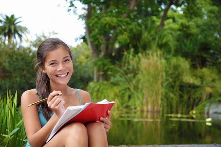 holding notes: Female student outdoors in the campus park studying and taking notes. Beautiful smiling mixed race caucasian  chinese young woman model.
