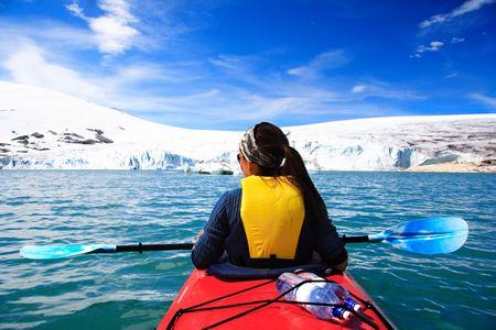 Kajak vrouw kajakken op de gletsjer meer in Jostedalsbreen, Noorwegen.