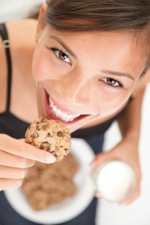 snacking: Woman eating cookie and drinking milk. Cute adorable beautiful young female model.