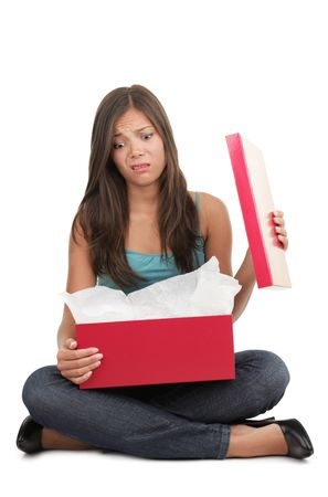 disappointment: Woman disappointed over gift. Beautiful mixed race caucasian  chinese young female model. Isolated on white background. Stock Photo