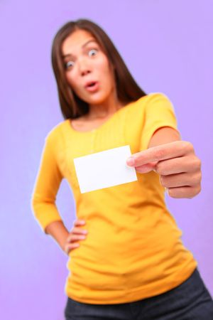 Surprised funny asian woman with business card. Beautiful cute mixed race caucasian / chinese young woman model presenting a blank business card on a purple background.  Stock Photo - 6549940