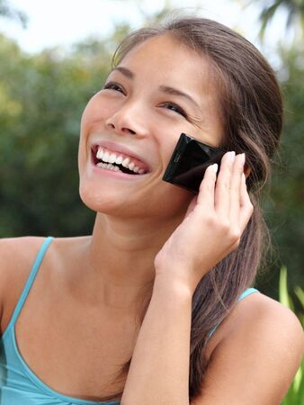 Beautiful smiling asian talking and laughing on the mobile phone. photo