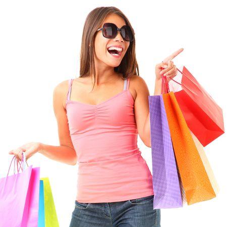 donna entusiasta: Lo shopping. Lo shopping donna eccitato e che punta a spazio dello copia. Immagine dinamica della giovane donna con le borse della spesa. Isolato su sfondo bianco.