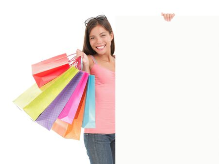 Shopping billboard sign. Shopping woman showing commercial sign. Picture of a beautiful young mixed race woman holding a blank billboard sign while standing with shopping bags. Isolated on white background. photo