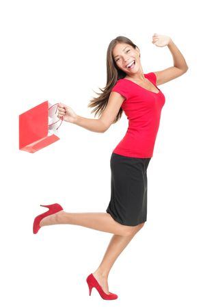 Shopping woman in joy running holding bag. Happy cheerful full length portrait of a beautiful mixed Chinese Asian  Caucasian young woman model running with a red shopping bag. This photo is isolated on white background.