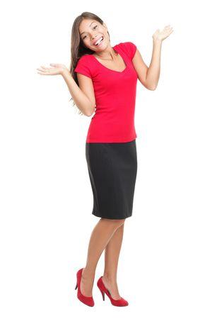 카메라 웃는 빨간 복장에 shrugging 행복 한 여자. 해피 스마일 젊은 아시아  백인 여성 모델 멀리 찾고 흰색 배경에 고립 된 혼합.