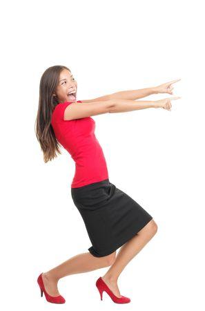 ragazza che indica: Donna di puntamento. Felice donna eccitata che punta lateralmente in piedi nel profilo di lunghezza completa. Isolato su sfondo bianco.  Archivio Fotografico