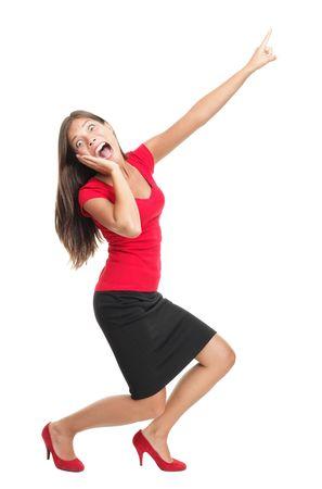 ascending: Gritando y se�alando la mujer. Imagen divertida de longitud completa de un modelo de cauc�sicos  chino, joven de raza mixta hermoso vestido casual en rojo. Aislado sobre fondo blanco.