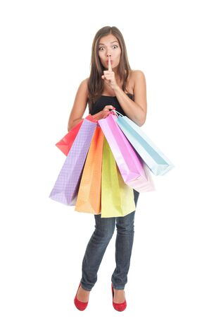 Shopping woman. Full length attractive shopping girl holding shopping bags saying hush. Isolated on white background. photo