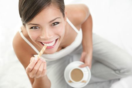 Coffee anc cookie woman. Beautiful Asian  Caucasian woman enjoying coffee with a cookie. photo