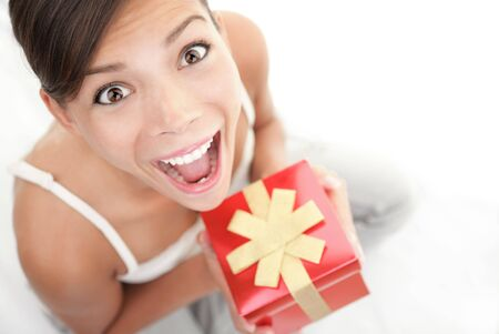 Happy excited woman holding gift  present. Cute surprised mixed Asian Chinese  Caucasian female model. photo