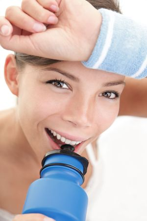 Fitness woman close-up. Sport woman with sweatband drinking water from blue sport bottle.  Stock Photo