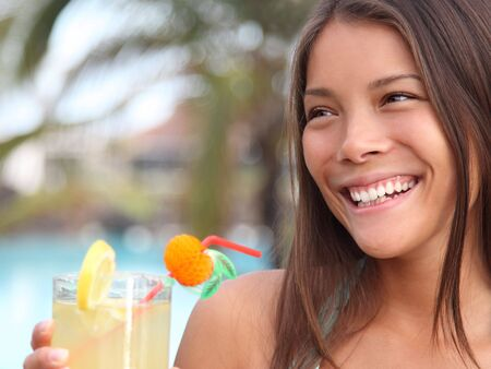 Summer holidays woman drinking alcoholic drink outside by the pool at a tropical resort. photo