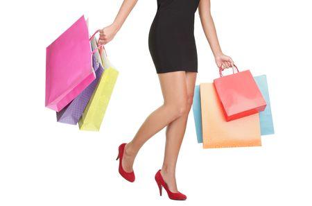 faldas: Mujer llevando bolsas de la compra de compras. disminuir la mitad cintura para abajo la imagen de piernas sexy en rojos los tacones altos y coloridos bolsas de la compra. Aislado sobre fondo blanco.  Foto de archivo