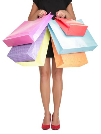 overspending: Shopping woman holding shopping bags. Closeup of beautiful women legs in red high heels and colorful shopping bags. Isolated on white. Stock Photo