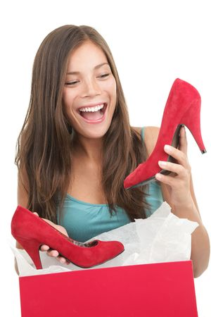 buying: Woman getting shoes as gift or happy of her shopping. Asian woman surprised and happy to receive red high heels shoes as a present. Isolated on white.