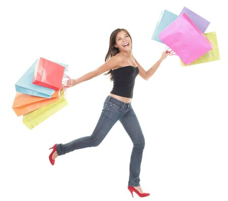 gastos: Shopping woman. Cheerful young woman running and jumping of joy holding shopping bags. Full length isolated on white background. Imagens