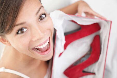 shoe boxes: Obtenci�n de zapatos como regalo de mujer. Mujer hermosa joven sorprendida y encantada de recibir los zapatos de tacones rojo como un regalo. Foto de archivo