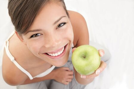 Apple woman holding green apple. Beautiful smiling young woman. Beautiful natural smiling healthy looking young woman. Stock Photo - 6813850