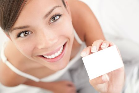 holding business card: Casual business card woman. High angle view of beautiful mixed race Asian Chinese  Caucasian young woman.