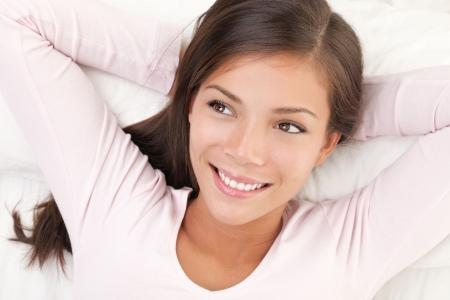 空想とベッドの中でリラックスした笑顔の女性。多民族国家中国白人若くて美しい女性モデル。 写真素材