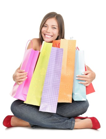 Shopping woman holding shopping bags sitting on the floor being very happy after the sale. Beautiful cute looking mixed Chinese Asian  Caucasian young woman model isolated on white background. Stock Photo