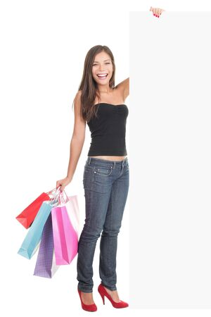 board: Woman shopping sign. Shopper showing blank billboard sign while standing with many shopping bags. Full length picture of a beautiful young mixed race woman isolated on white background.