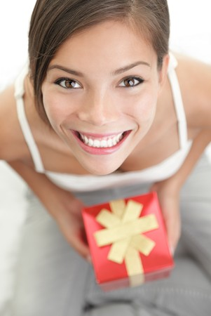 Happy cute woman holding gift  present. Smiling mixed Asian Chinese  Caucasian female model. Stock Photo