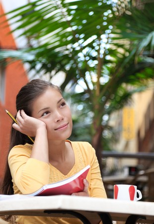 Woman university student at cafe outdoor studying. Asian female college student thinking. Young Asian-Caucasian woman model outside.