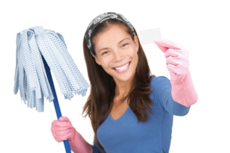 Cleaning woman holding white sign or business card with copy-space. Isolated on white background. Shallow depth of field, focus on sign.