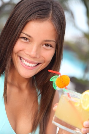 holidays: Vacation woman enjoying drink in tropical resort. Gorgeous multiracial Asian  Caucasian woman young woman in bikini during summer holidays.
